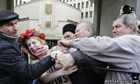 A Femen protester against Vladimir Putin's policies concerning Ukraine is detained near the Crimean parliament in Simferopol.